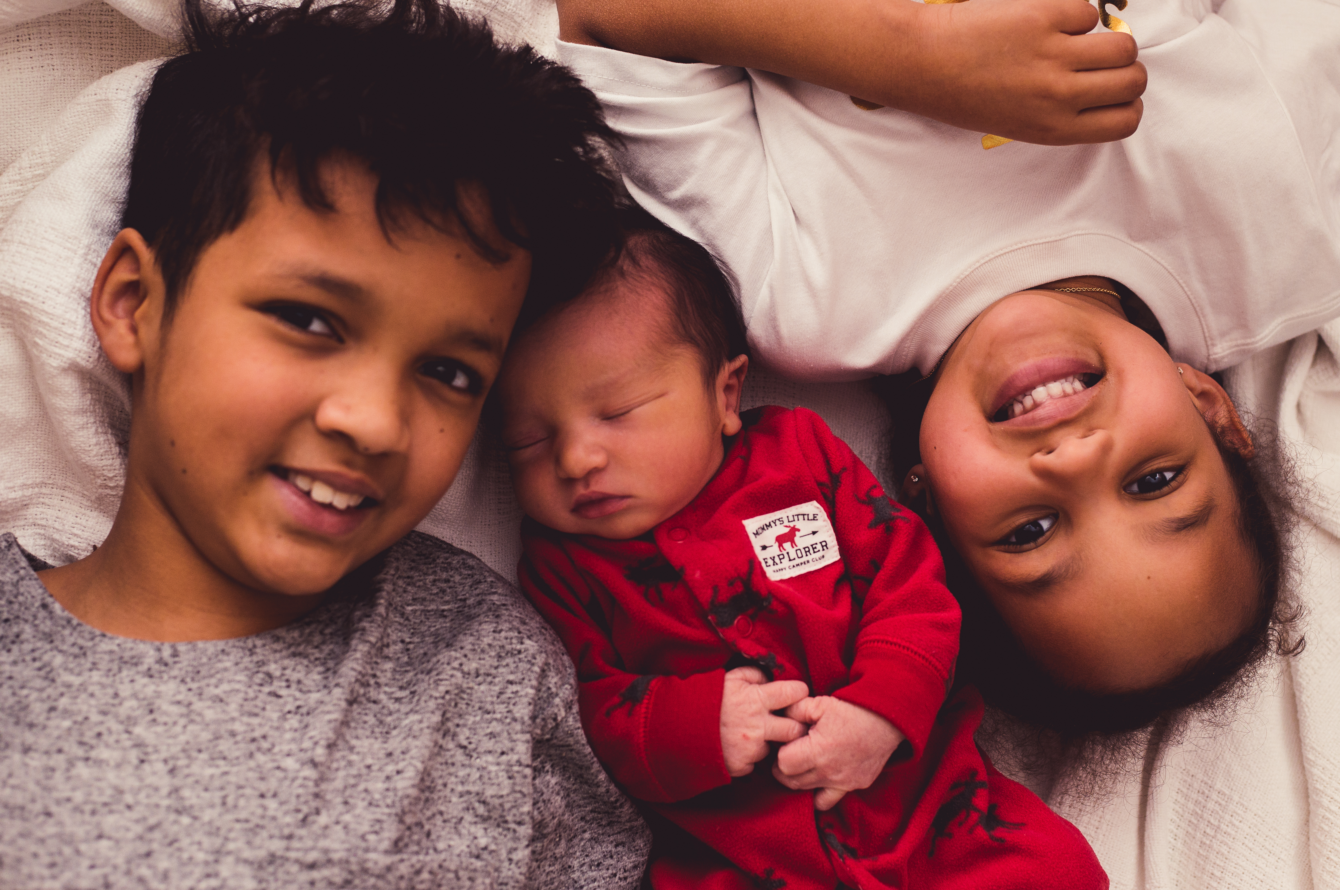 overhead shot of broth and sister with newborn brother in the middle