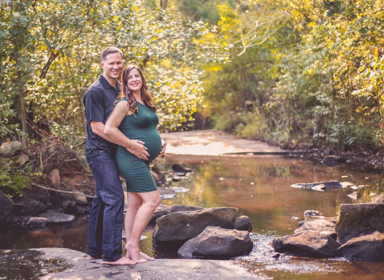 a pregnant woman and her husband stand on a rock by a stream