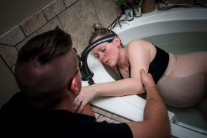 Woman labors at home in bathtub with her husband next to her for support