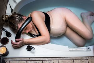 Woman labors at home in the bathtub during home birth
