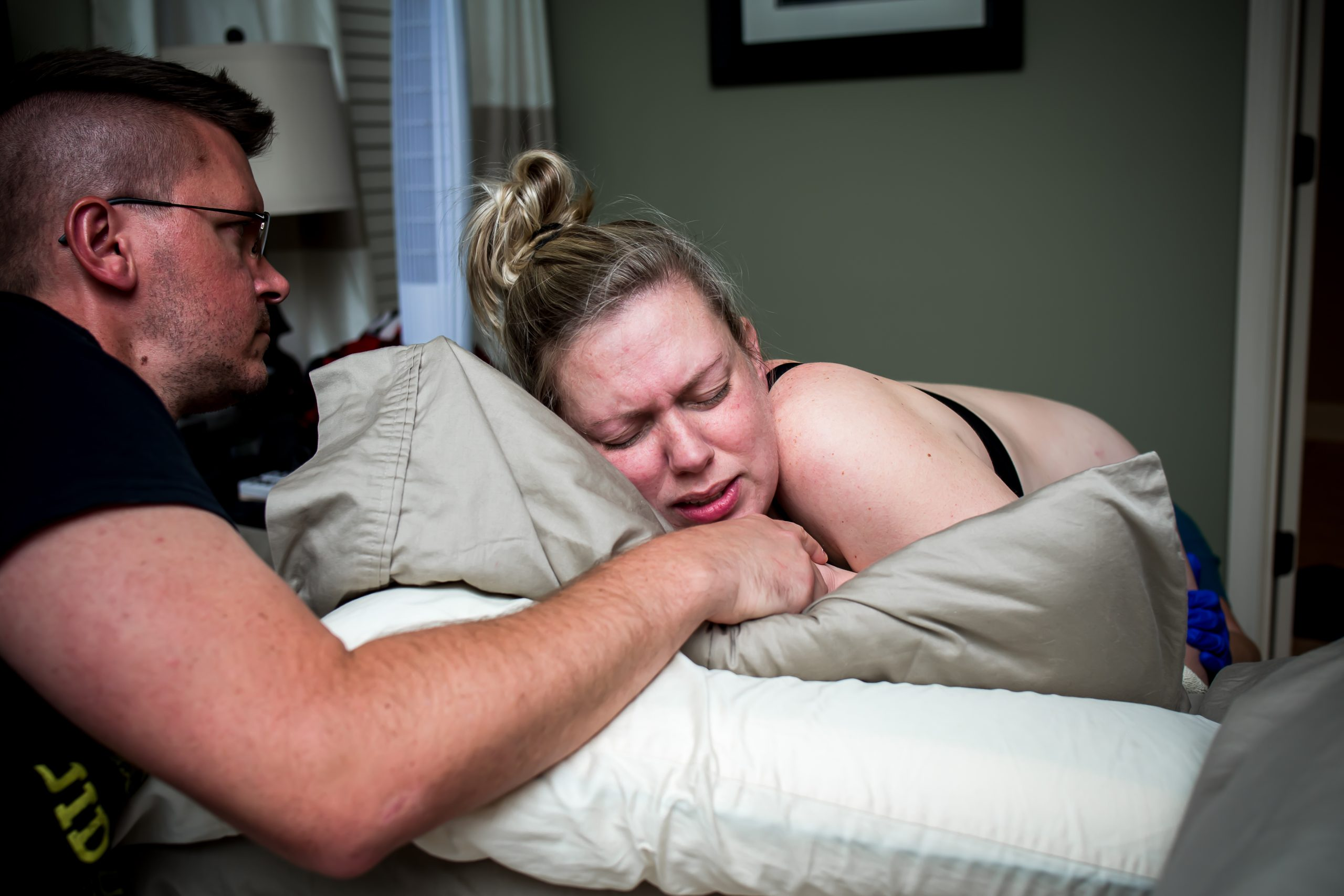 Woman labors at home leaning on her bed during home birth her husband is in front of her for support